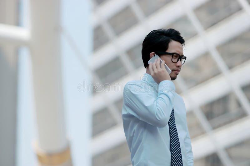 年轻亚裔商人画象谈话在他的工作的电话在室外街道背景 库存图片