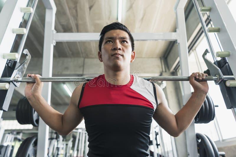 年轻亚裔在健身房的人举的杠铃 健康生活方式 库存照片