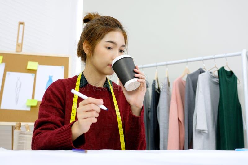 年轻亚裔在办公桌的妇女时尚编辑运作的和饮用的咖啡在演播室背景,小企业主,时尚中 免版税库存照片