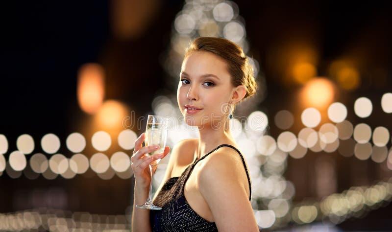 年轻亚裔在圣诞节的妇女饮用的香槟 免版税库存照片