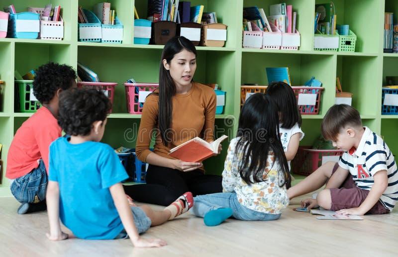 年轻亚裔在幼儿园classroo的妇女老师教的孩子 免版税库存照片