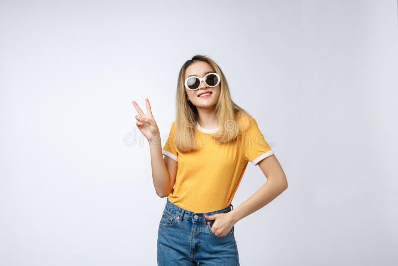 年轻亚裔在被隔绝的背景陈列的妇女佩带的太阳镜和指向与手指第二一会儿 免版税库存照片