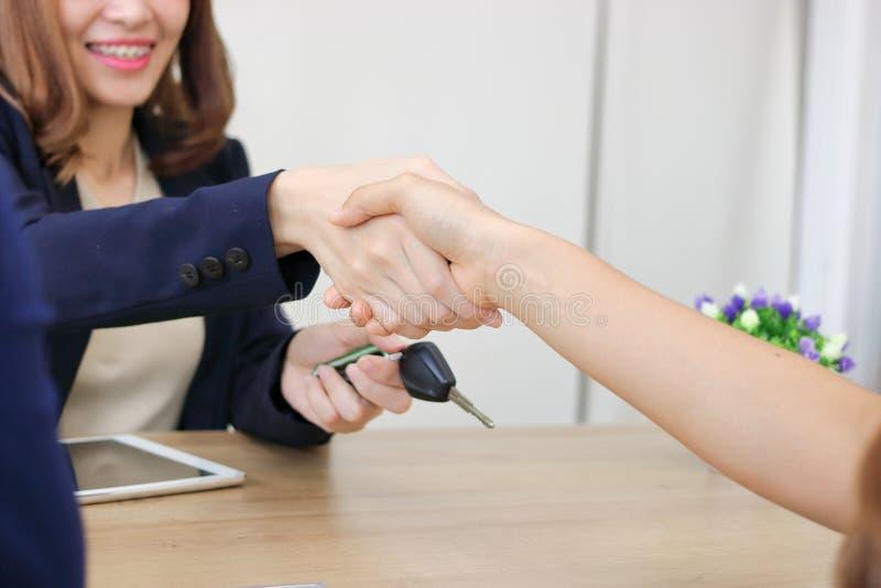 年轻亚裔女商人与伙伴握手在完成会议以后 握手问候成交概念 免版税库存照片