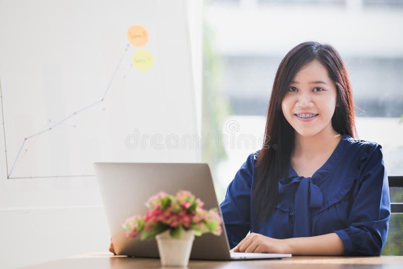 年轻亚裔女商人集中了工作到膝上型计算机选项 库存图片