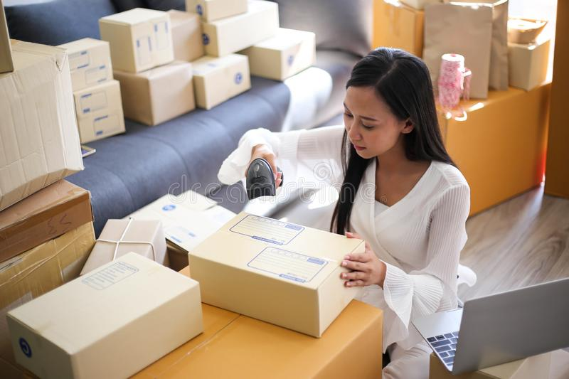 年轻亚裔女孩是自由职业者发动写地址的小企业主在纸板箱在工作场所,运输购物 图库摄影