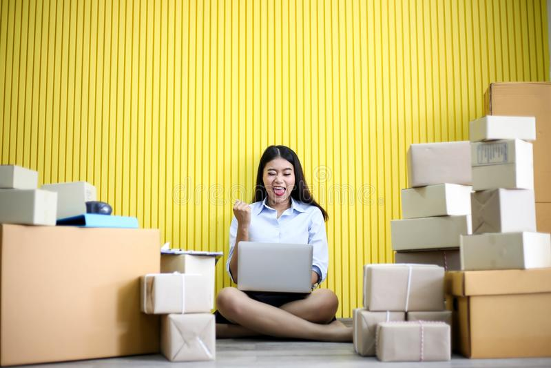 年轻亚裔女孩是自由职业者发动写地址的小企业主在纸板箱在工作场所,运输购物 免版税库存图片