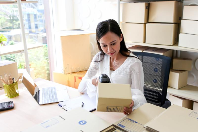 年轻亚裔女孩是自由职业者发动写地址的小企业主在纸板箱在工作场所,运输购物 库存图片