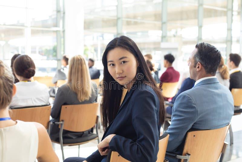 年轻亚裔女实业家在会议室坐了,微笑对照相机 图库摄影