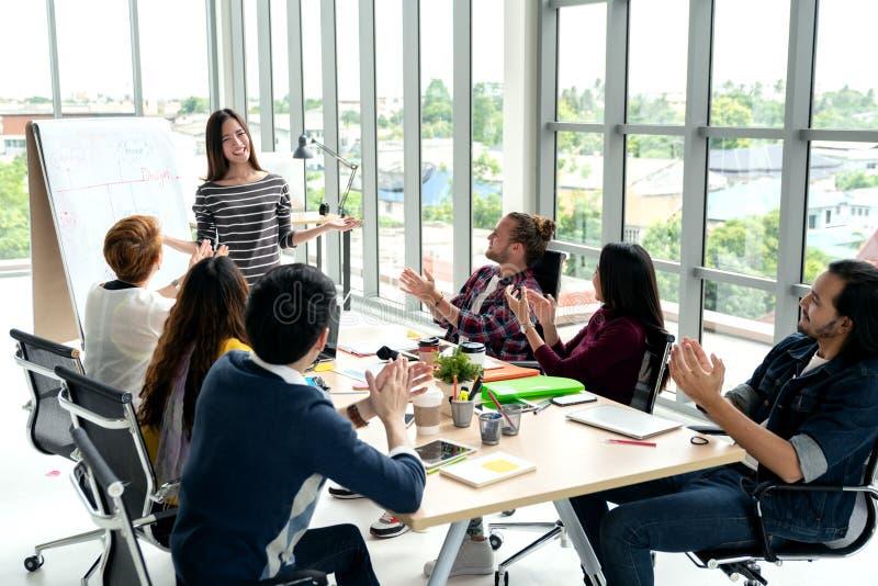 年轻亚裔女实业家解释想法对小组创造性的不同的队在现代办公室 库存照片