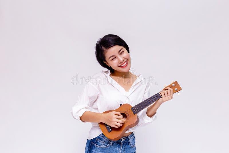 年轻亚裔女性女孩在白色被隔绝的背景中的弹尤克里里琴海滩吉他 免版税库存图片