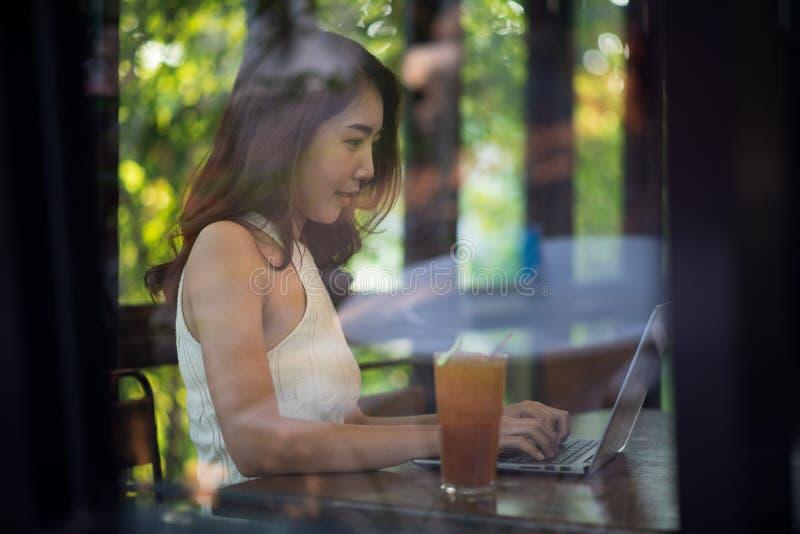 年轻亚裔妇女与在桌上的膝上型计算机,企业概念,射击一起使用通过玻璃窗 库存图片