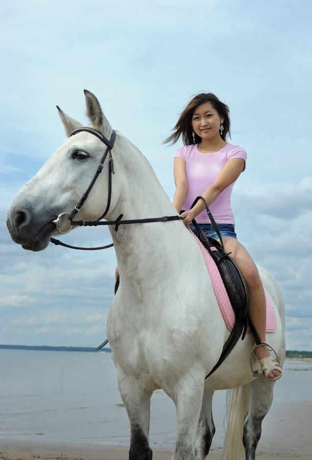 年轻亚裔妇女乘坐的白马 免版税库存图片