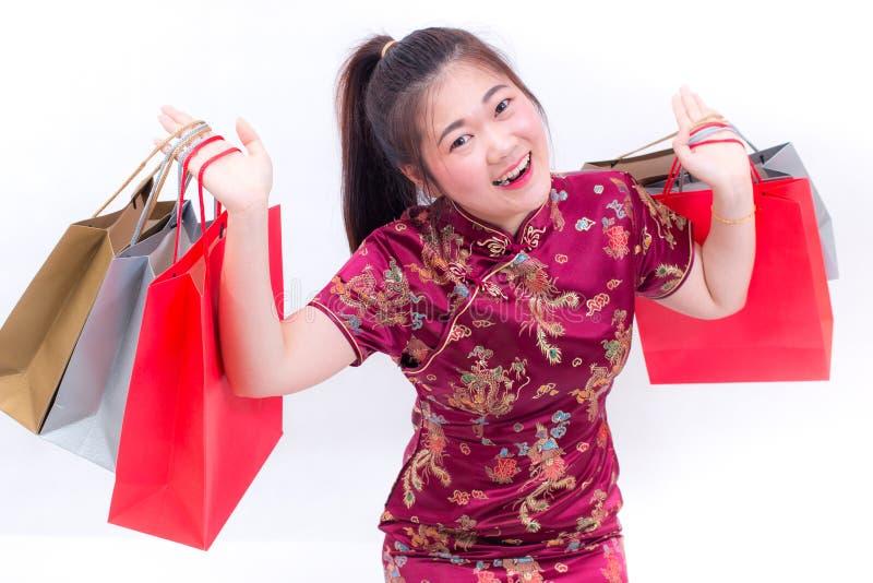 年轻亚裔妇女佩带的汉语穿戴与运载购物袋的传统cheongsam并且微笑 中国新年度 免版税图库摄影