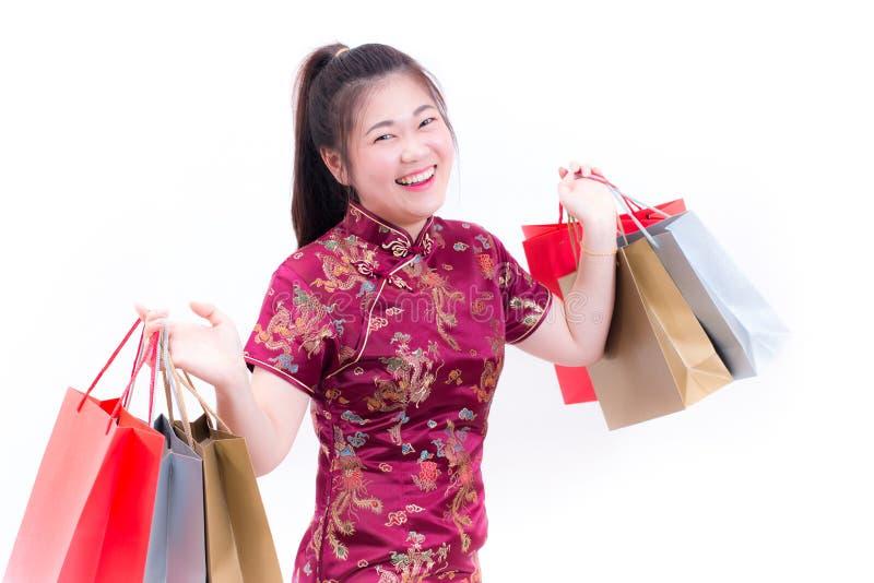 年轻亚裔妇女佩带的汉语穿戴与运载购物袋的传统cheongsam并且微笑 图库摄影