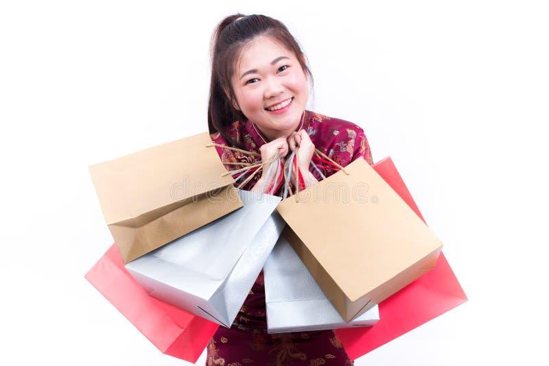 年轻亚裔妇女佩带的汉语穿戴与运载购物袋的传统cheongsam并且微笑 免版税库存图片