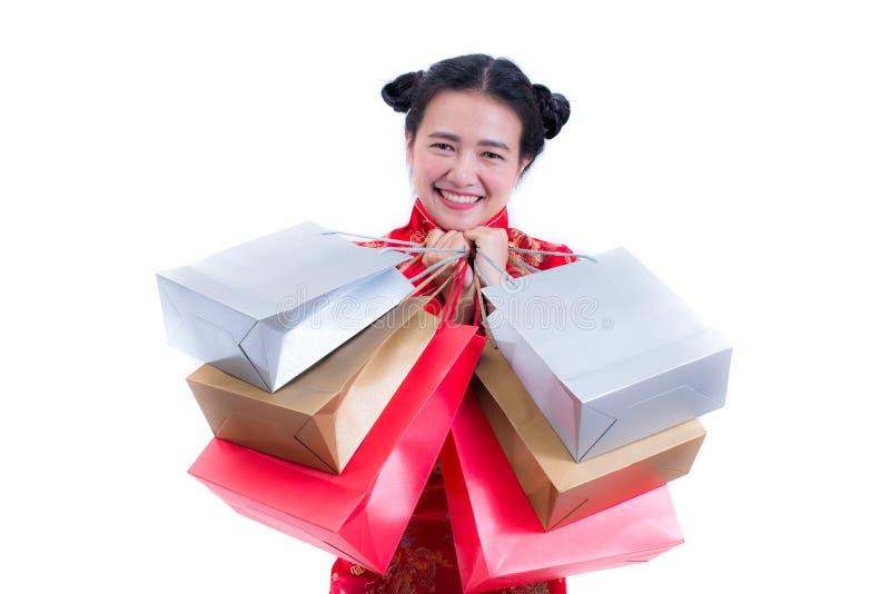 年轻亚裔妇女佩带的汉语穿戴与运载购物袋的传统cheongsam并且微笑 免版税库存照片