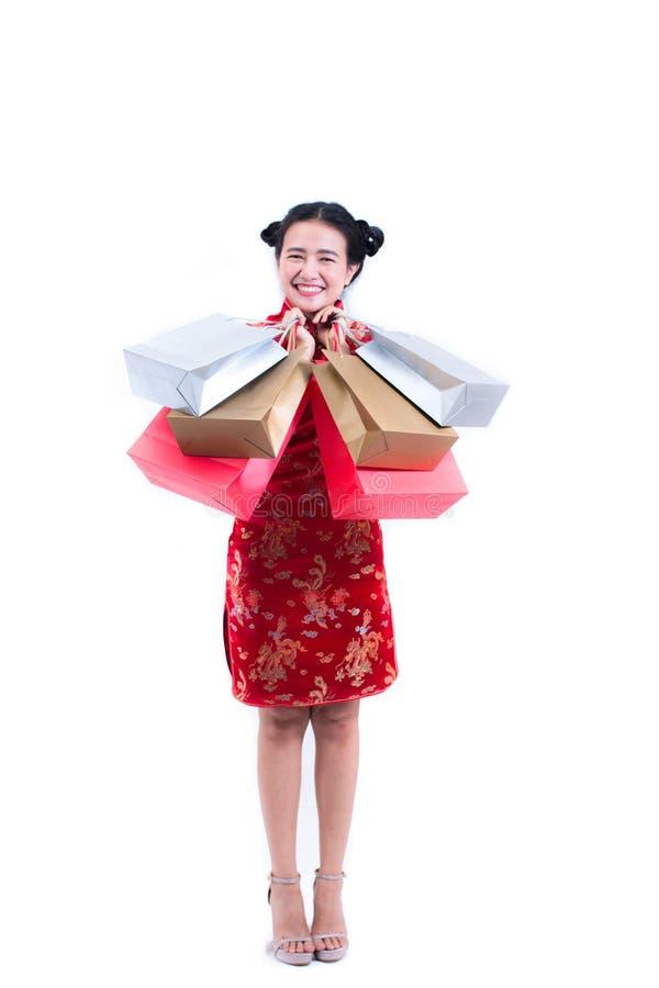 年轻亚裔妇女佩带的汉语穿戴与运载购物袋的传统cheongsam并且微笑 库存图片