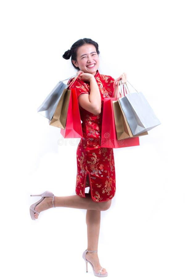 年轻亚裔妇女佩带的汉语穿戴与运载购物袋的传统cheongsam并且微笑 库存照片
