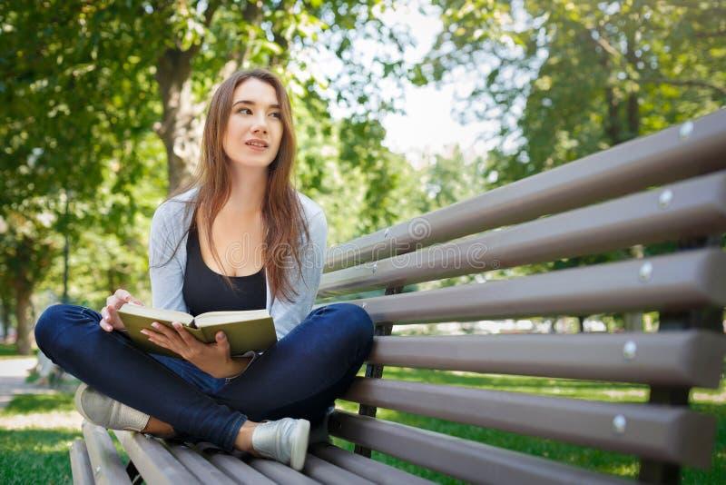 年轻亚裔妇女坐一条长凳在公园 放松和读书 图库摄影