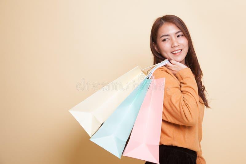 年轻亚裔妇女满意对购物袋 库存照片