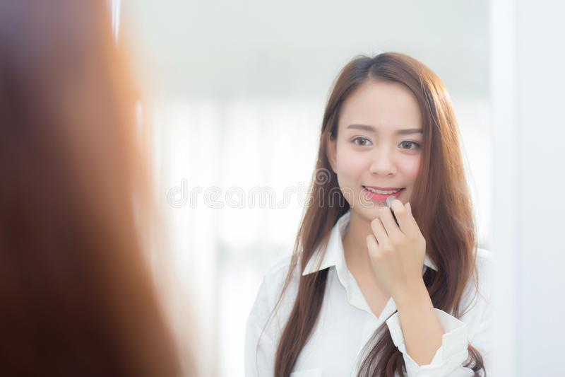 年轻亚裔妇女画象秀丽拿着和看构成唇膏的镜子的 免版税库存图片