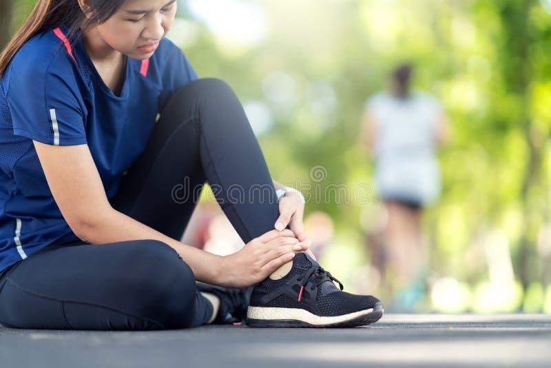 年轻亚裔妇女遭受的踝关节损伤 赛跑者女孩由扭伤脚腕受伤,当跑或行使时 母赛跑者 免版税库存图片