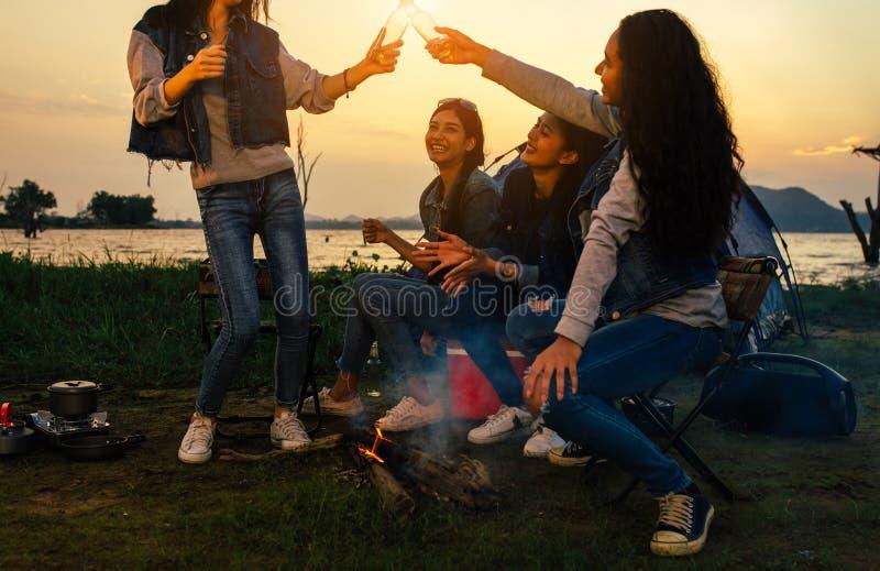 年轻亚裔妇女野营的饮用的啤酒党和一起烹调野餐的朋友 库存图片