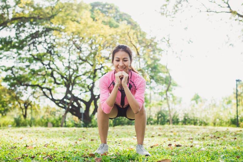 年轻亚裔妇女锻炼的蹲坐加强她的秀丽身体在公园包围与绿色树和温暖的阳光 免版税库存图片