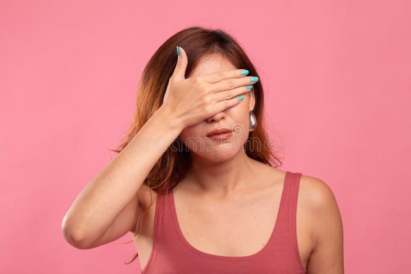 年轻亚裔妇女闭上她的眼睛用手 库存图片