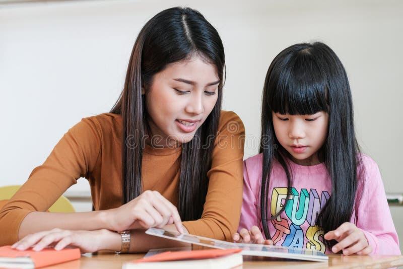 年轻亚裔幼儿园classroo的妇女老师教的女孩 库存照片