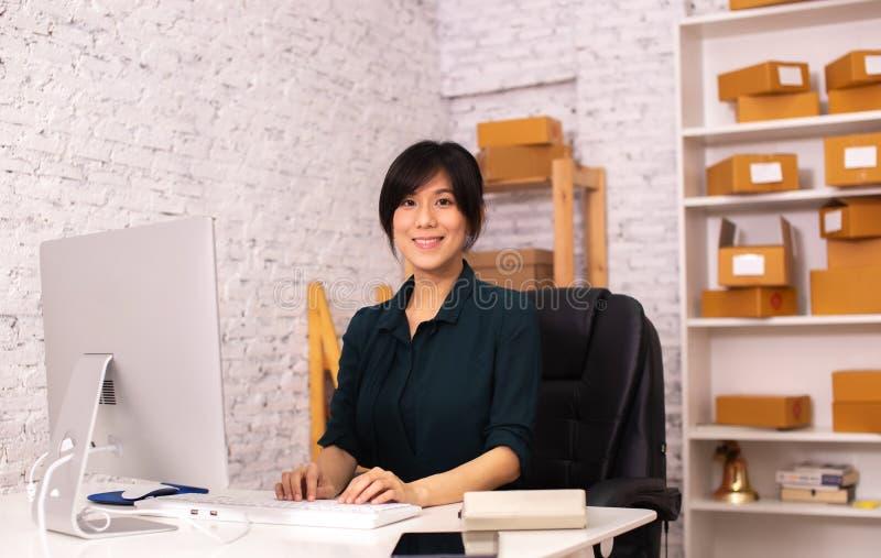 年轻亚裔成人女商人在运作在网上公司的办公室 免版税库存图片