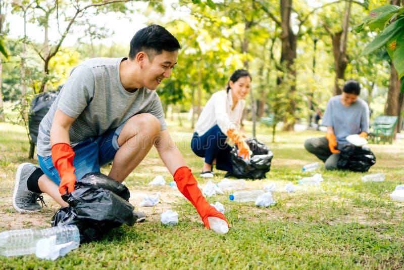 年轻亚裔戴着橙色手套和收集在垃圾袋的男人和妇女垃圾在公园 免版税库存图片