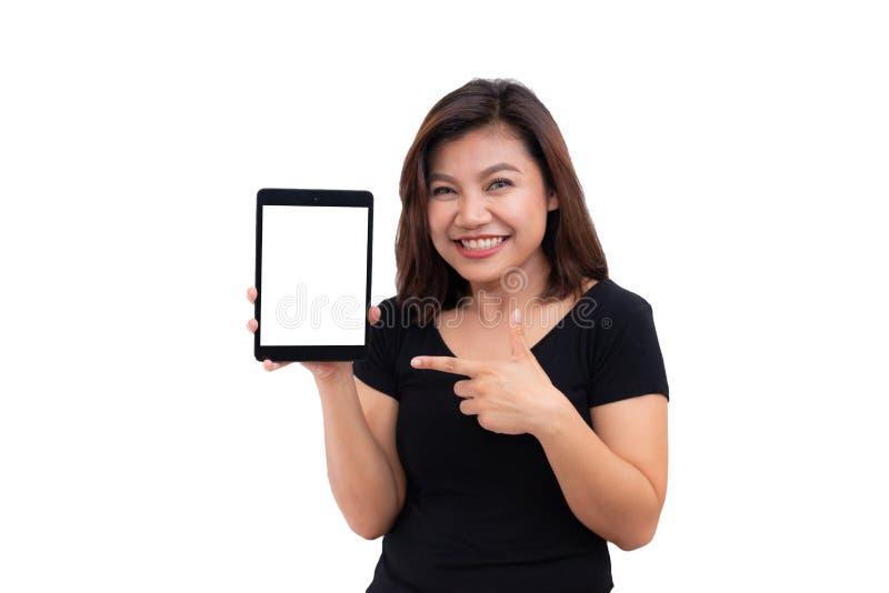 年轻亚裔拿着片剂计算机的妇女黑发 使用黑屏数字式片剂计算机个人计算机愉快的微笑的妇女 库存照片