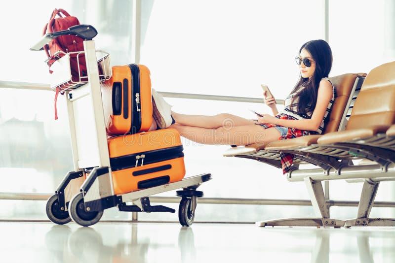 年轻亚裔旅客妇女,大学生使用智能手机在机场、行李和袋子坐台车推车 免版税库存照片