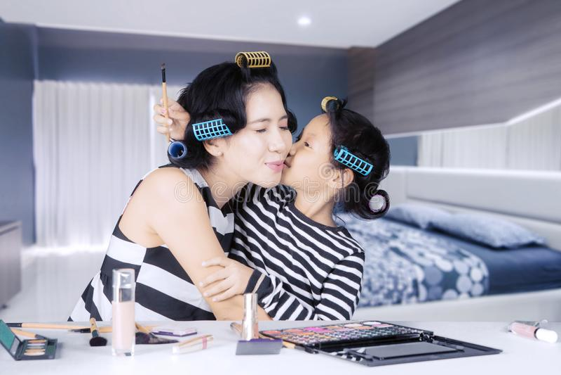 年轻亚裔母亲和女儿有卷发夹的在家花费质量时间 免版税库存图片