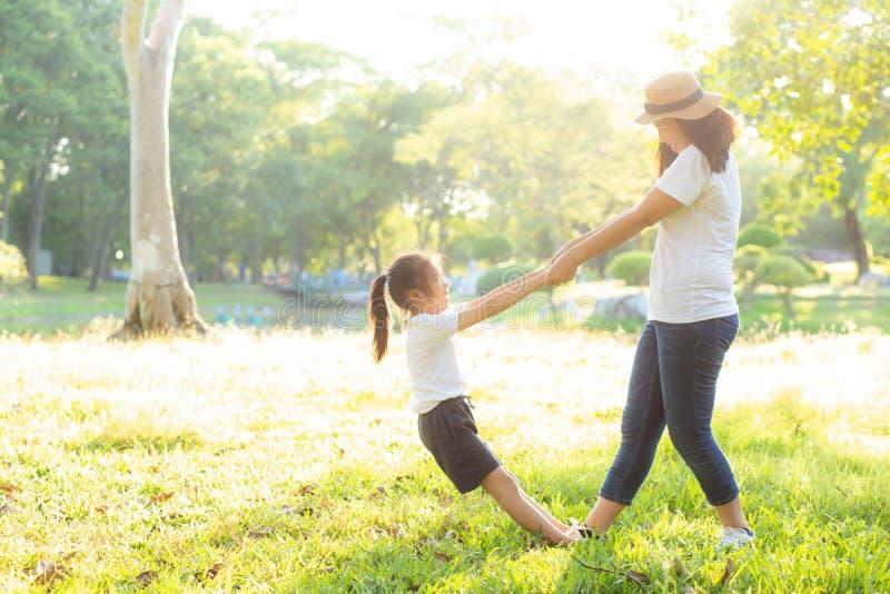年轻亚裔母亲和小女儿播放有乐趣的公园和幸福,家庭一起享用和放松和休闲 库存照片