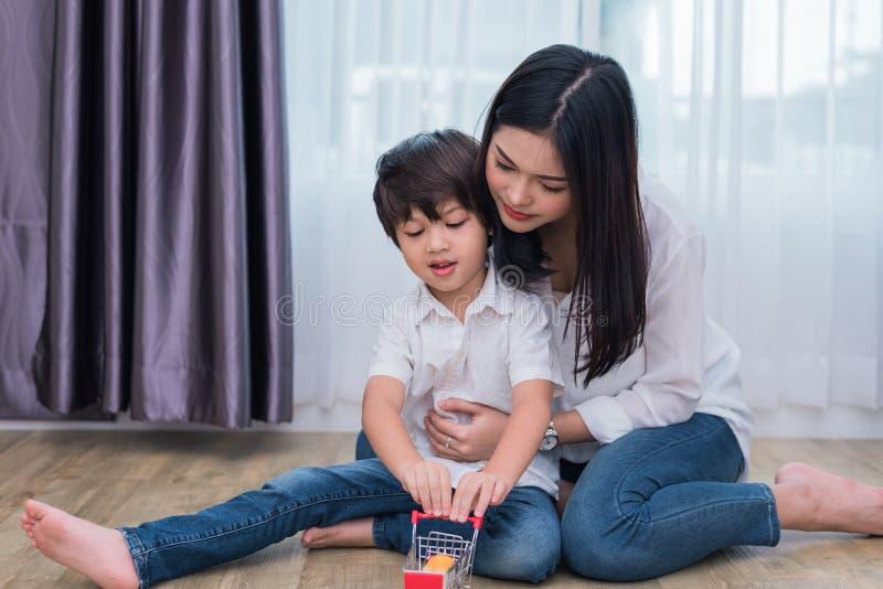 年轻亚裔演奏玩具的妈妈和儿子在房子里 母亲和儿子概念 r 学龄前和后面 免版税库存图片