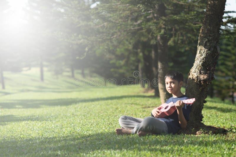 年轻亚裔男孩有演奏ukelele的乐趣时间在公园在晴朗的早晨 免版税库存图片