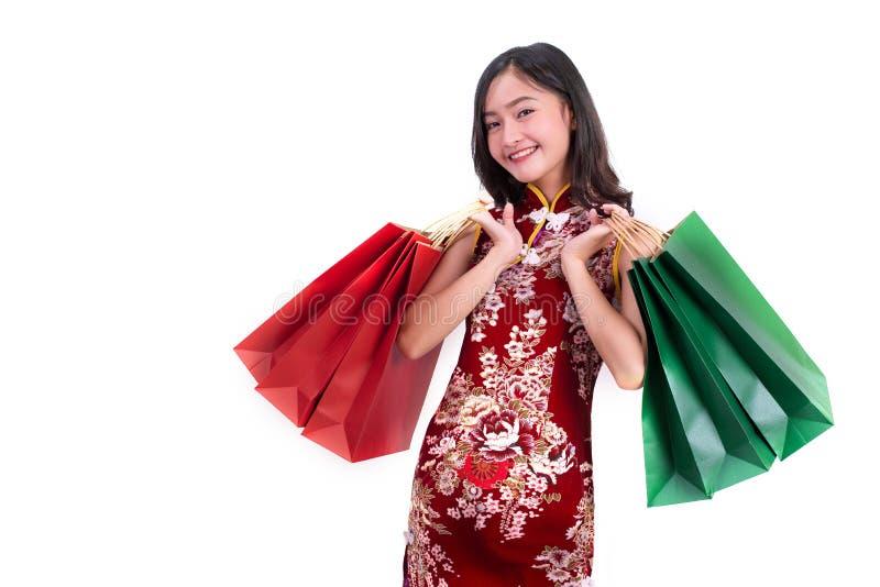 年轻亚裔秀丽妇女佩带的cheongsam和拿着红色和绿色购物带来在春节节日事件打手势  库存照片