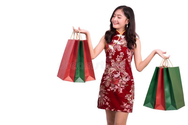 年轻亚裔秀丽妇女佩带的cheongsam和拿着红色和绿色购物带来在春节节日事件打手势  图库摄影