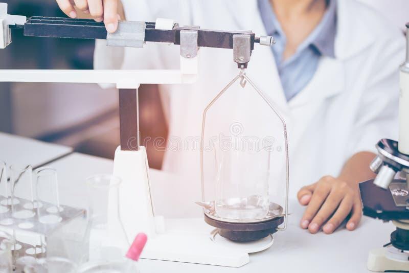 年轻亚裔科学家是在实验科学的某些活动象开发医学的混合的化学制品或词条数据, 免版税库存照片