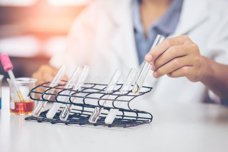 年轻亚裔科学家是在实验科学的某些活动象开发医学的混合的化学制品或词条数据, 图库摄影
