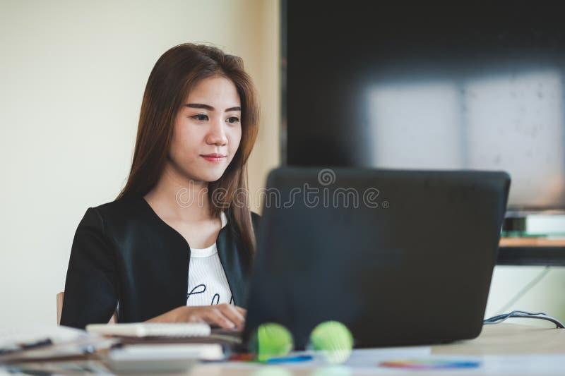 年轻亚裔秘书女性与膝上型计算机一起使用 库存图片