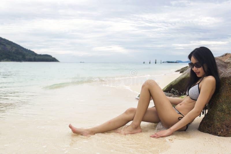 年轻亭亭玉立的亚裔说谎在海岩石、海和波浪的妇女佩带的比基尼泳装作为背景 图库摄影