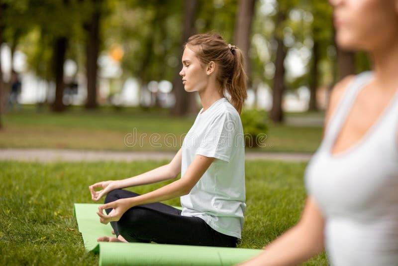 年轻亭亭玉立的女孩在与做与其他女孩的结束眼睛的莲花坐坐锻炼在绿草在公园 库存图片