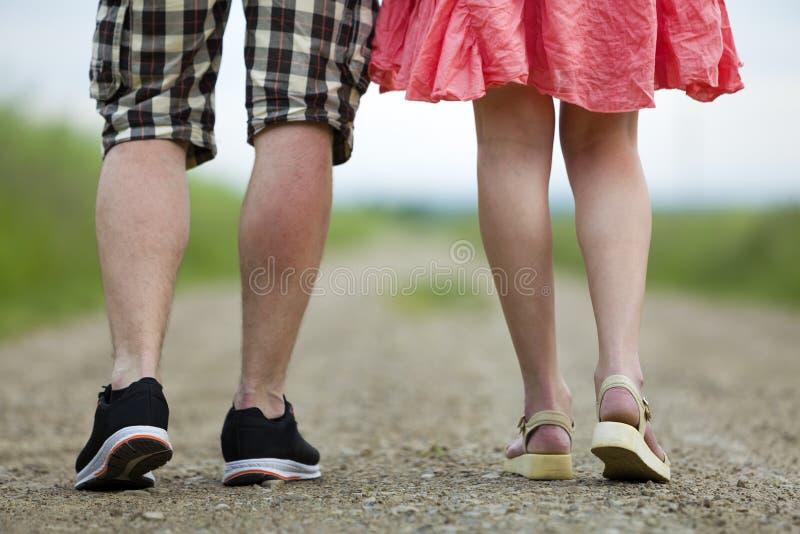 年轻亭亭玉立的妇女的腿后面看法红色简而言之一起走由地面路的礼服和人的在晴朗的夏日  图库摄影