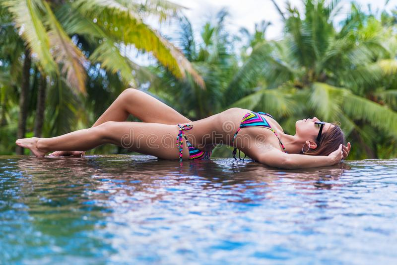 年轻亭亭玉立的深色的妇女在热带游泳池晒日光浴 免版税库存图片
