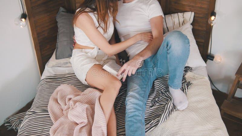 年轻亲吻人和的女孩拥抱和,当在床上时 库存照片