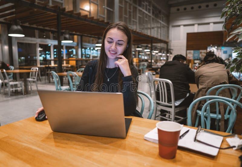 年轻人、美女与膝上型计算机一起使用和饮用的咖啡在一张木桌上 免版税库存照片