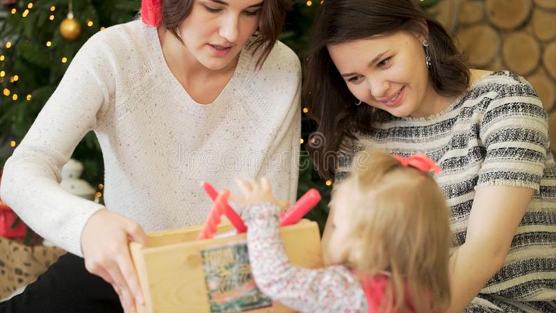 年轻人、美好的女同性恋的夫妇和他们的可爱宝贝女孩在圣诞树旁边与红色蜡烛和诗歌选,新年 库存照片